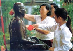 Buddhist devotees pour water over the statue